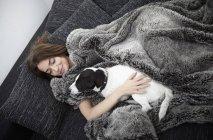 Молода жінка, загорнуті в хутра ковдру розслабляючий на дивані з собака — стокове фото