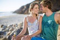 Jovem casal feliz compartilhando uma bebida na praia — Fotografia de Stock