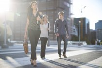 Three people walking on city square — Stock Photo