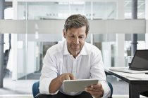 Businessman in office looking at digital tablet — Stock Photo