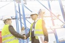 Dos hombres usando ropa protectora estrecharme la mano en el puerto de contenedores - foto de stock