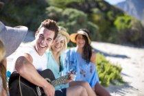 Друзья, общение на пляже и играть на акустической гитаре — стоковое фото