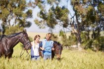 Young couple walking with horses in field — Stock Photo