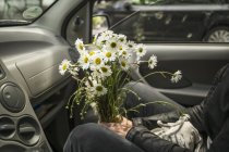 Woman sitting with daisies flowers in car — Stock Photo