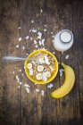 Bowl of granola, banana slices and coconut flakes — Stock Photo