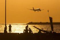 Indonésia, Bali, Jimbaran, pôr do sol no oceano com o avião no céu — Fotografia de Stock