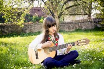 Girl sitting on a meadow playing guitar — Stock Photo