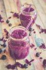 Deux verres de smoothie aux betteraves à la myrtille sur une surface en bois avec des ingrédients — Photo de stock