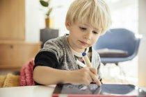 Retrato de menino de desenho com uma caneta digital na tablet digital em casa — Fotografia de Stock