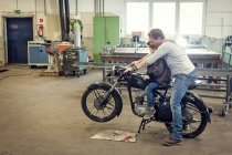 Father and son maintaining vintage moped in workshop — Stock Photo