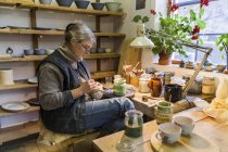 Potter in workshop painting a bowl — Stock Photo