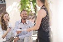 Empregada de mesa com a bandeja e o casal que estava ao ar livre degustação vinho tinto — Fotografia de Stock
