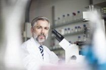 Портрет ученого в лаборатории с микроскопом — стоковое фото
