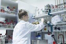 Femme biologiste travaillant en laboratoire — Photo de stock