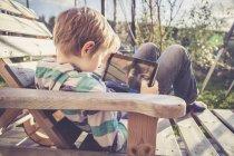Menino brincando com tablet digital em cadeira de plataforma de madeira — Fotografia de Stock