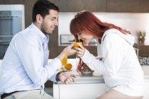 Couple in kitchen making fresh orange juice — Stock Photo