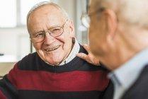 Due amici anziani sorridenti che parlano a casa — Foto stock