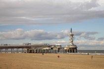 Нидерланды, Гаага, Шевенинген, Пирс на пляже под облаками — стоковое фото