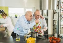 Senior friends cooking in kitchen together — Stock Photo