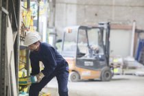 Warehouseman in storehouse lifting sack — Stock Photo