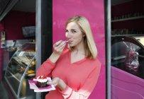 Mujer rubia sonriente comiendo pastel frente a un puesto de mercado - foto de stock