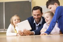 Teacher with pupils using digital tablet in classroom — Stockfoto