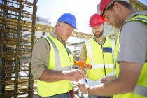 Строители обсуждают план строительства на строительной площадке — стоковое фото
