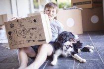 Garçon assis avec son chien et des boîtes dans une nouvelle maison — Photo de stock