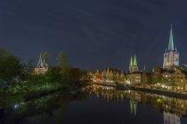 Deutschland, Lübeck, Stadtbild bei Nacht mit Kirchenbau Wasseroberfläche reflektieren — Stockfoto