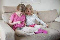 Дві сестри з цифрових tablet на дивані — стокове фото
