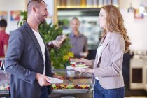Businessman and businesswoman having fruit from salad bar — Stock Photo