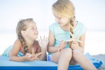 Dos chicas sonrientes tumbadas en un lilo con estrellas de mar en la playa — Stock Photo