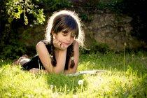 Дівчина лежав на луг, читати книгу — стокове фото