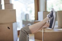 Moving house, woman's feet on a box — Stock Photo