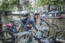 Нідерланди, Амстердам, усміхається жінка блокування її велосипеді перед місто канал — стокове фото