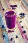 Verre de smoothie à la betterave à la myrtille avec graines de chia sur une surface en bois minable colorée — Photo de stock