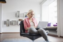 Woman sitting with laptop on leather chair at home — Stock Photo