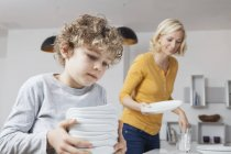 Mother and son laying the table — Stock Photo