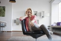 Portrait of woman sitting on leather chair at home — Stock Photo