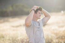 Giovane uomo in piedi nel campo, guardando altrove — Foto stock