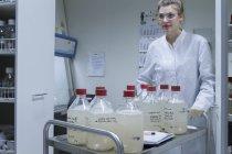 Biologiste en laboratoire poussant chariot avec bouteilles — Photo de stock