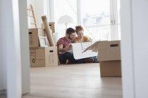 Молодая пара в новой квартире с картонными коробками с планом заземления — стоковое фото