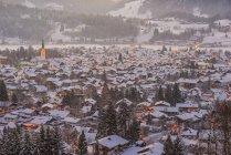 Germania, Baviera, Mostra al coperto di neve illuminato Oberstdorf a penombra — Foto stock