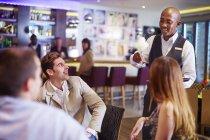 Cameriere al bar dell'hotel che serve cocktail per uomini d'affari — Foto stock