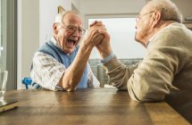 Two senior friends arm wrestling at home — Stock Photo