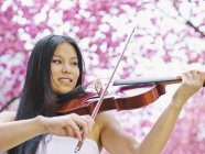 Portrait of female viola player in front of blossoming cherry tree — Stock Photo