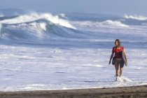 Indonesia, Bali, woman carrying surfboard at seafront — Stock Photo
