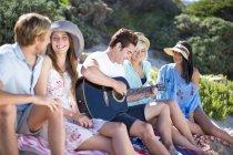 Друзі спілкування на пляжі і грає акустична гітара — стокове фото