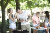 Friends on holiday grilling sausages and listening to music on a digital tablet — Stock Photo