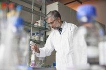 Ученый, дозирование в лаборатории — стоковое фото